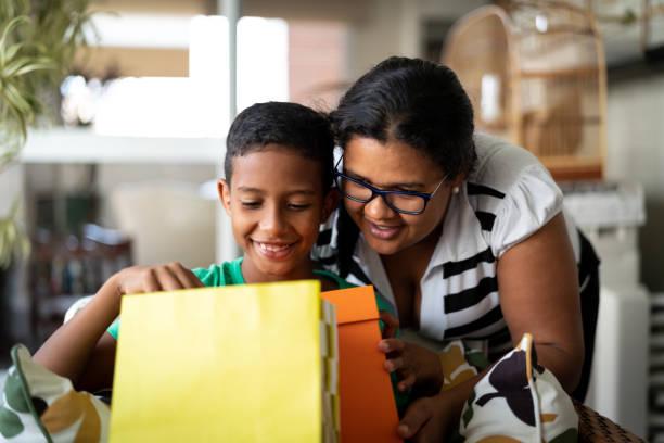 mutter und sohn umarmt und annahme von geschenken - mütter oder kindertag - alles gute zum geburtstag sohn stock-fotos und bilder