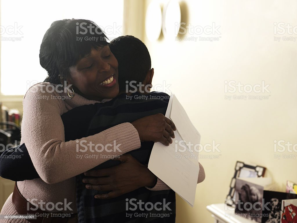Mother and son (12-13) embracing at home 免版稅 stock photo