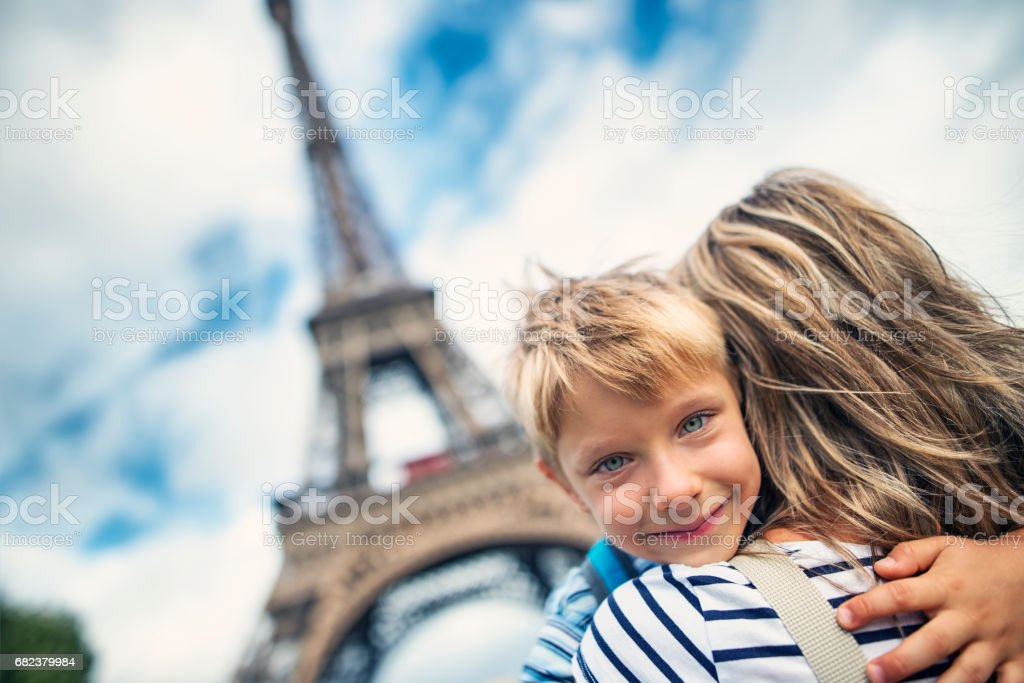 Mother and son embracing in front of the Eiffel Tower in Paris, France royalty-free stock photo