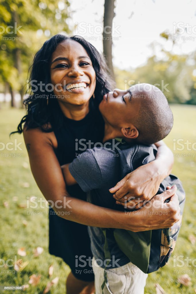 mother and son embracing in the park stock photo