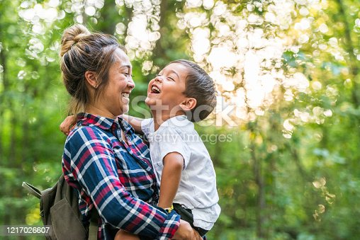 A young mixed-race mother and son enjoy time in nature together.  The mother is holding her toddler son in her arms as they stand together in the woods.   The sun is shining through the green leaves of the trees and they are sharing a laugh together.