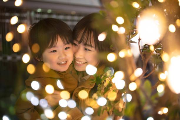 moeder en zoon genietend van kerstverlichting - christmas family stockfoto's en -beelden