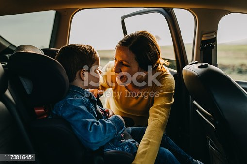 Mother and son cuddling at back of a car