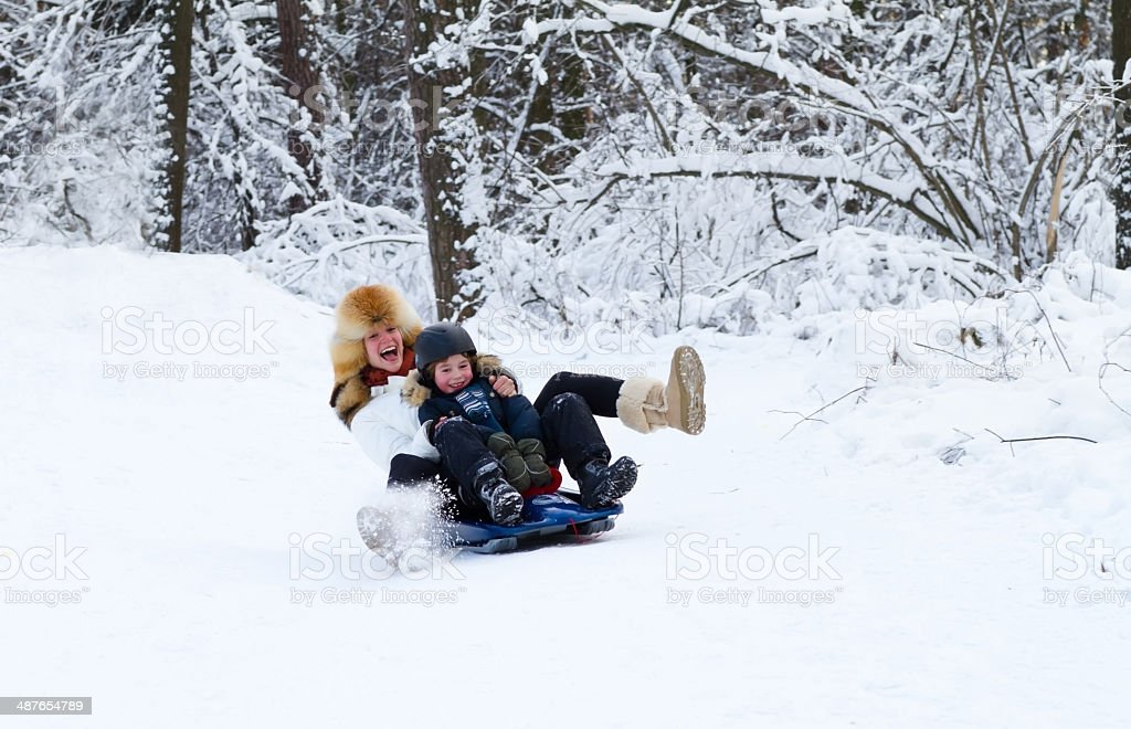 Mother and son enjoying sleigh ride on beautiful winter day stock photo