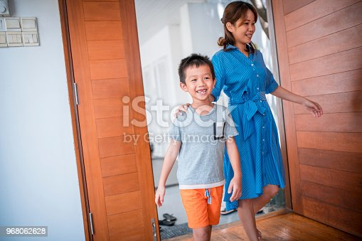 670900812istockphoto Mother and son entering their home 968062628