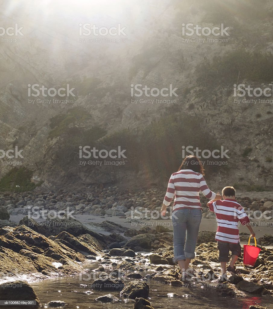 Mother and son (6-7) exploring seashore, rear view 免版稅 stock photo