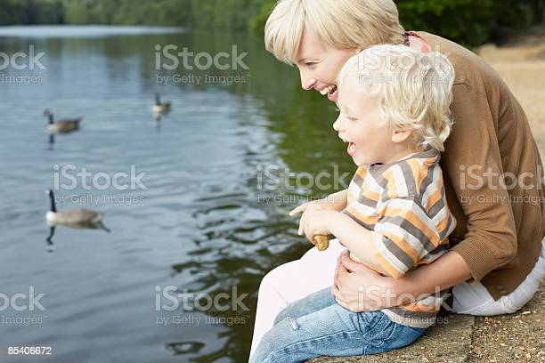 Photo of Mother and son feeding ducks in pond