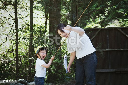 An asian mother helping her son fishing.