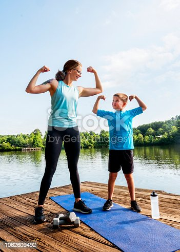 Mother and son exercising together outdoors on a dock by a lake.