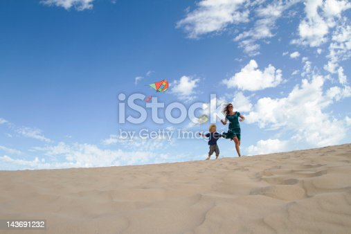 453383283 istock photo Mother and son flying kite on beach 143691232