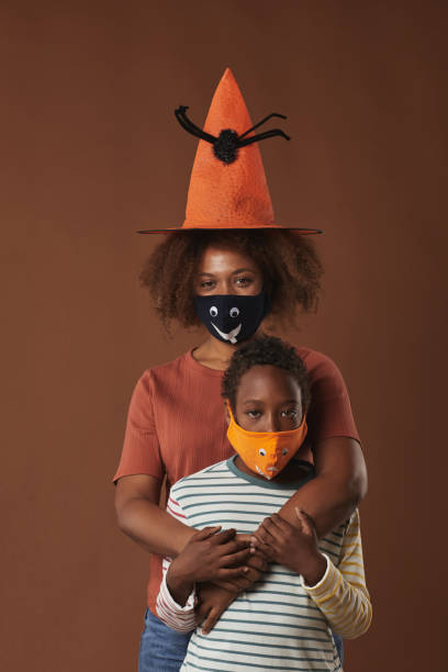 Mother And Son Halloween Studio Shot Vertical studio portrait of modern young woman wearing witch hat standing with her her cute son both wearing protective masks, brown background halloween covid stock pictures, royalty-free photos & images