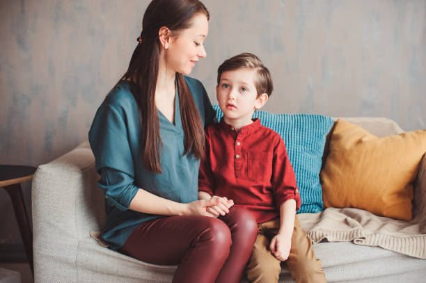 mother and son happy together at home, sitting at cozy couch. Moving to new home concept, casual family modern life stock photo