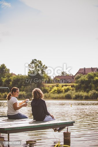 A mother and her young son have hot tea by the river