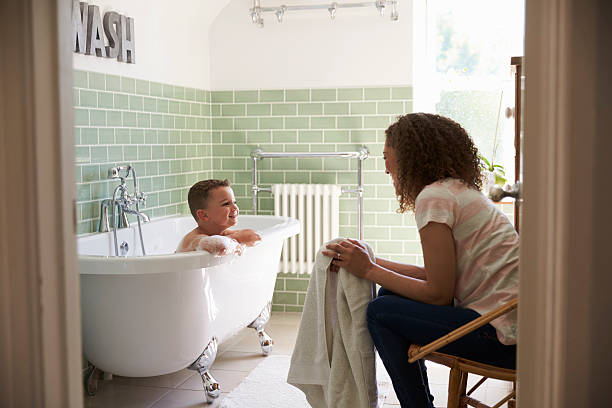 Mother And Son Having Fun At Bath Time Together stock photo