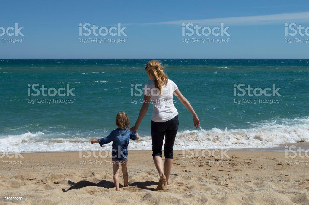 Moeder en zoon plezier op het strand royalty free stockfoto