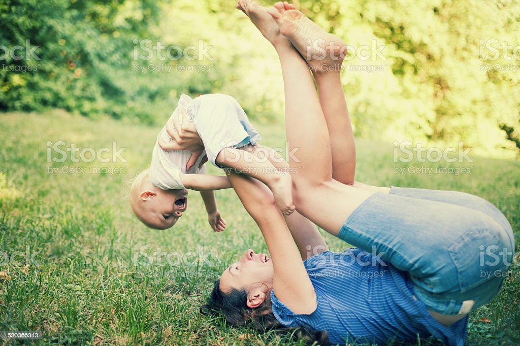 Mother and son having fun on the grass stock photo