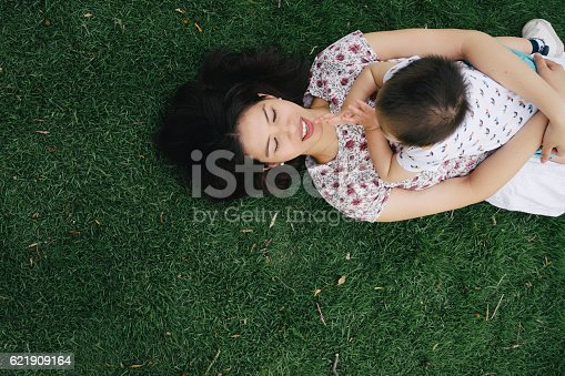 istock Mother and son having fun together in a park 621909164