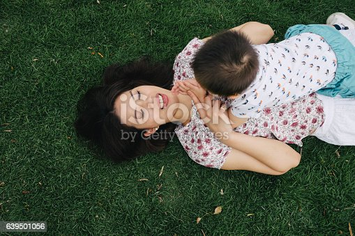 istock Mother and son having fun together in a park 639501056