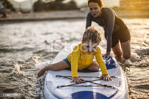 Mother and son having fun with paddle board in the sea.