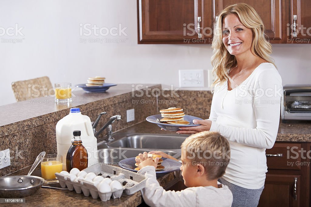 Mother and son having pancakes for breakfast stock photo