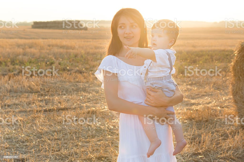 Mother and son. Hay stack or bale on yellow field. royalty-free stock photo