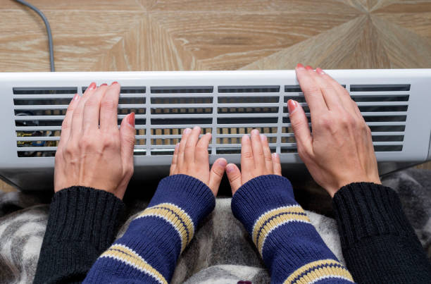 mutter und sohn eine hand vor einer elektrischen heizung heizung - heizraum stock-fotos und bilder