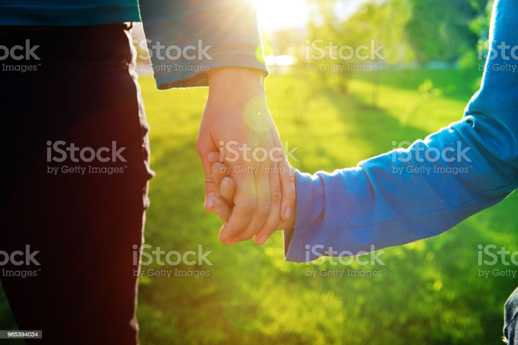 mother and son holding hands at sunset, parenting royalty-free stock photo