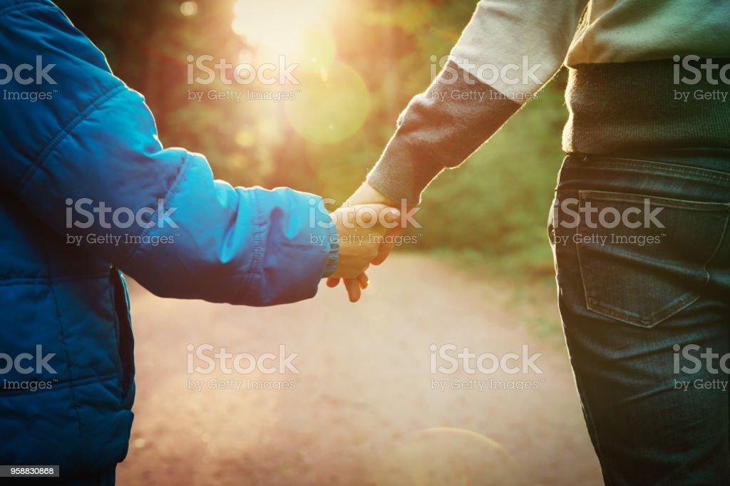 母と息子の夕日自然で手をつないで ストックフォト