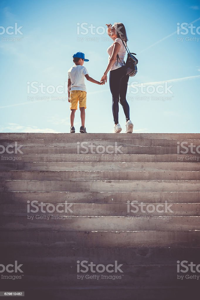 Photo which show mother and son holding hands and stay on the top of...