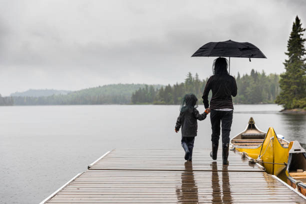 Mother and Son Holding Hands on Dock by the Lake stock photo