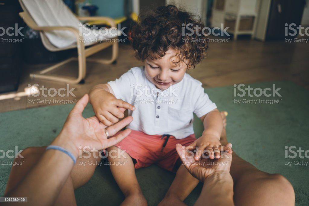 Happy Mother and son holding hands on the floor at home