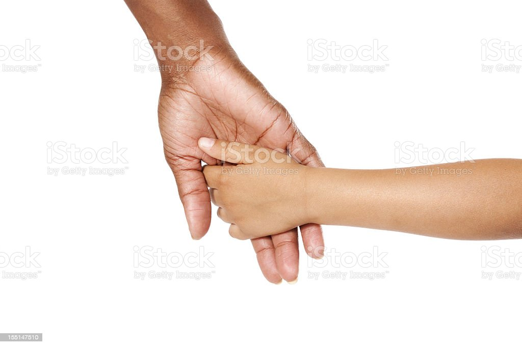 Mother and son holding hands. Woman is African American and the young...