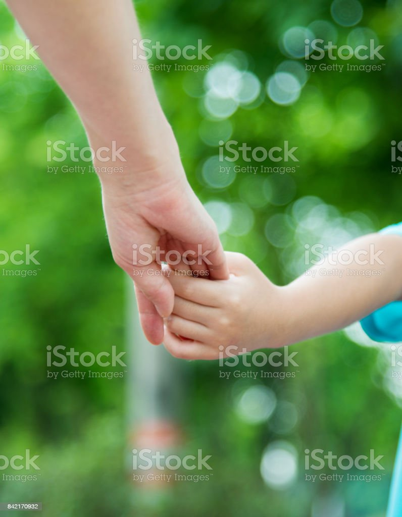Mother and son holding hands at summer nature outdoor.