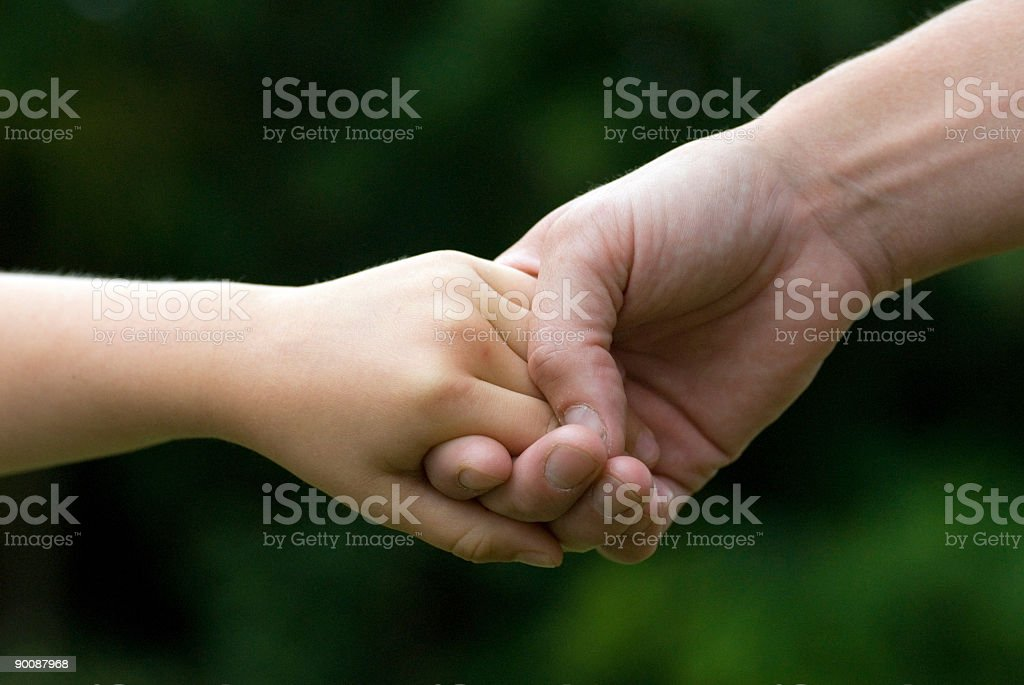 Mother holding sons hand for safety, tight clench of hands.