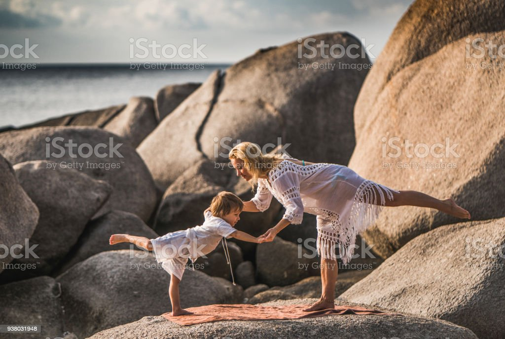 Young mother and her small son cooperating while exercising balance...