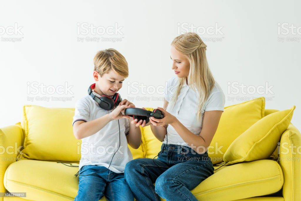 mother and son holding headphones on yellow sofa isolated on white stock photo