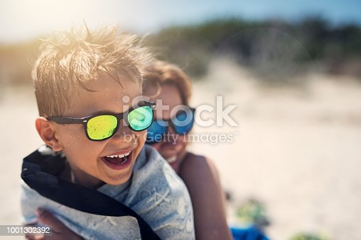 Mother and son hugging and laughing on beach. Sunny summer day on beach. Nikon D850