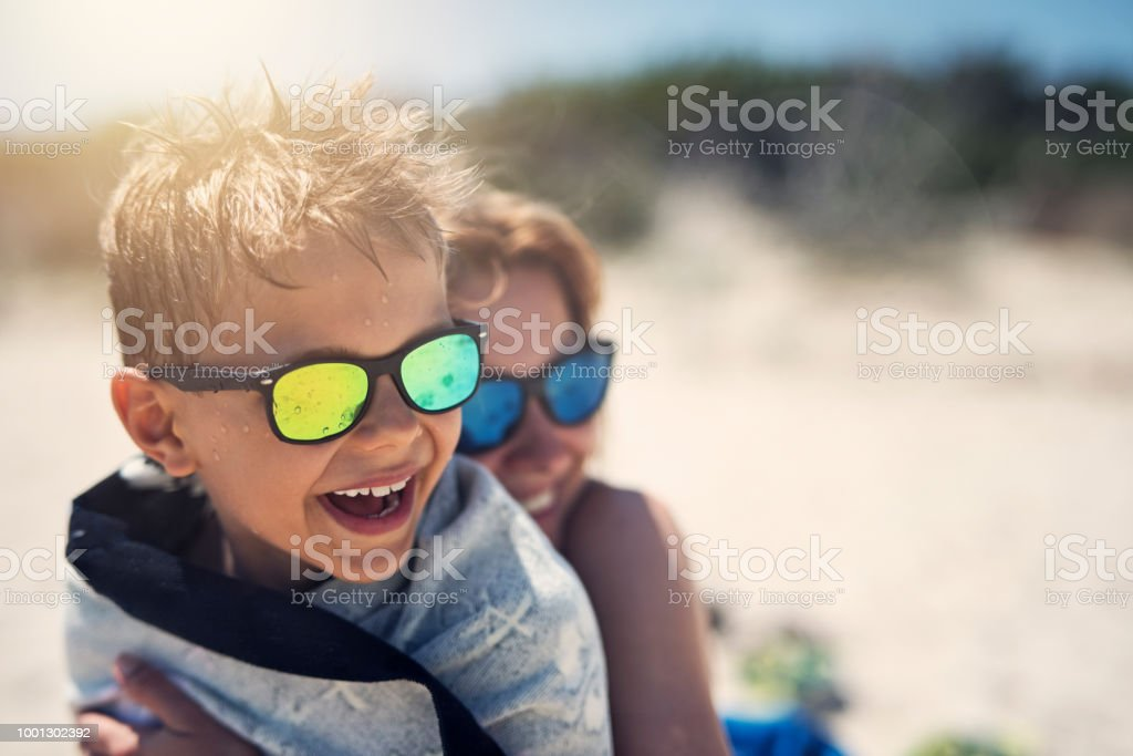 Mutter und Sohn umarmen und lachen am Strand – Foto