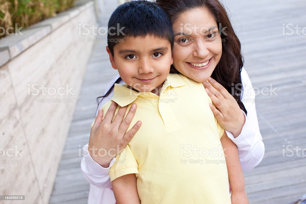 A mother and son hugging and looking ahead stock photo