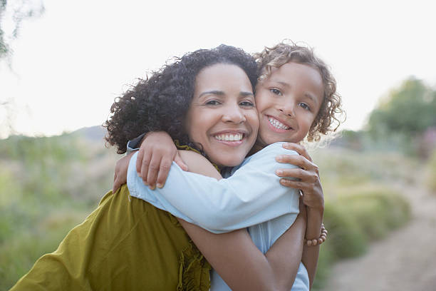Mother and son hugging outdoors stock photo