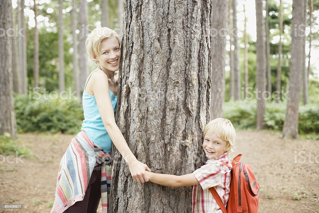 Mother and son hugging tree in woods royalty-free stock photo