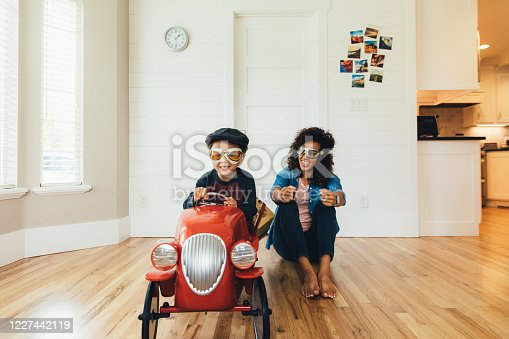 A mother and her young son imagine traveling on the open roads. The boy sits in a red toy car while his mom sits next to him on the floor inside their home. Sometimes a little imagination and a staycation is exactly what a child needs.