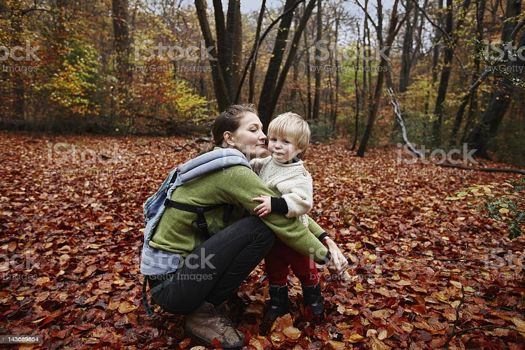 Mother and son in autumn leaves stock photo