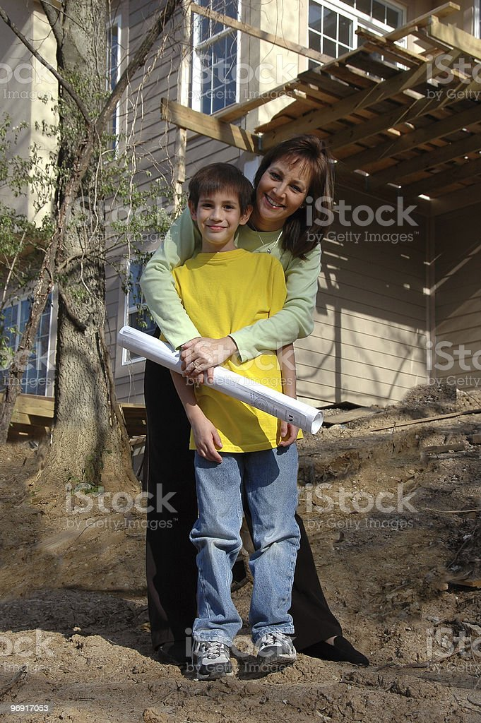 Mother and son in front of house under construction royalty-free stock photo