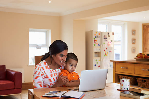 Mother And Son In Kitchen Looking At Laptop Together stock photo