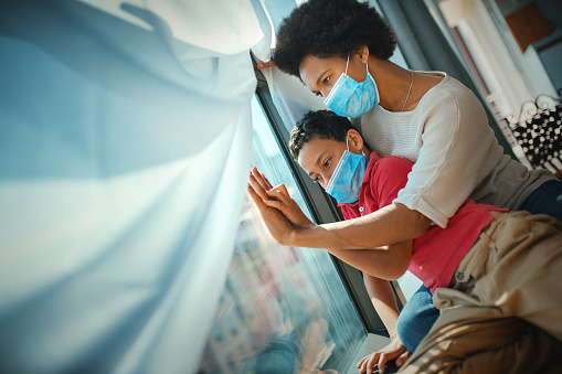 Mother and son in pandemic quarantine looking though window.