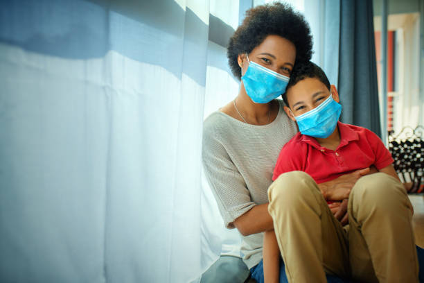 Mother and son in pandemic quarantine looking though window. stock photo