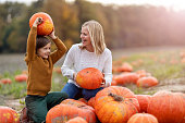 Mother and son in pumpkin patch field