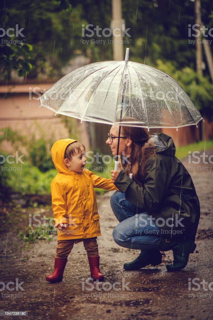 Mother and son in raincoats under umbrella in rain stock photo