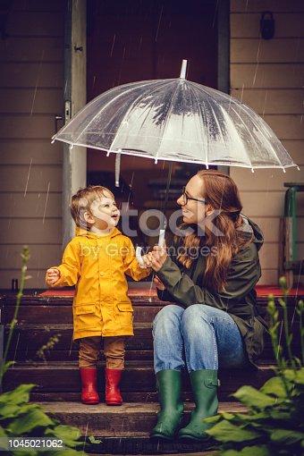 Family walking under rain in autumn